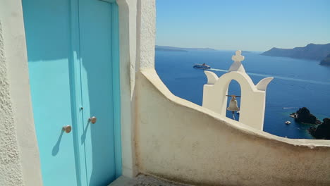 A-cruise-ship-in-the-distance-behind-a-Greek-Island-church-with-a-blue-door