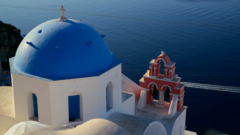 A-boat-passes-a-Greek-Orthodox-church-on-the-Greek-island-of-Santorini