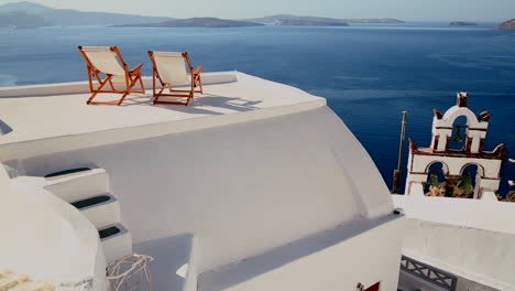 Pan-across-deck-chairs-sit-on-a-beautiful-balcony-in-the-Greek-Islands