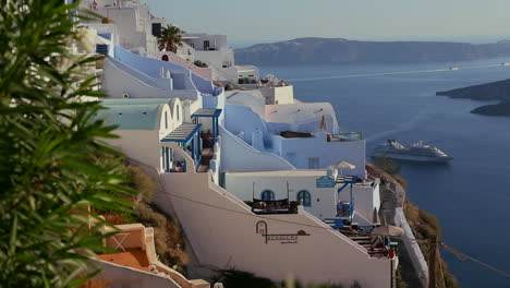 White-houses-line-the-hillsides-of-the-Greek-Island-of-Santorini-with-a-cruise-ship-in-the-distance