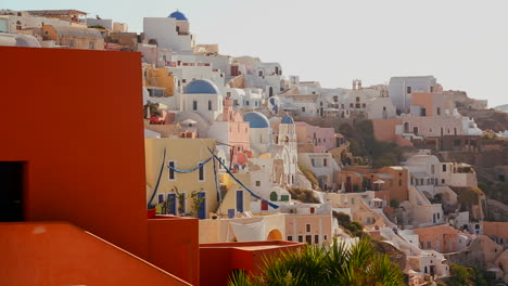 Multi-colored-houses-line-the-hillsides-of-the-Greek-Island-of-Santorini-with-a-Greek-flag-in-the-distance
