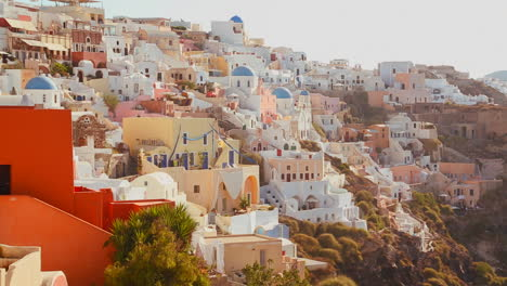Multi-colored-houses-line-the-hillsides-of-the-Greek-Island-of-Santorini-with-a-Greek-flag-in-the-distance-1