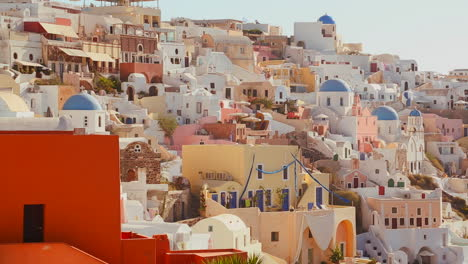 Multi-colored-houses-line-the-hillsides-of-the-Greek-Island-of-Santorini-with-a-Greek-flag-in-the-distance-2