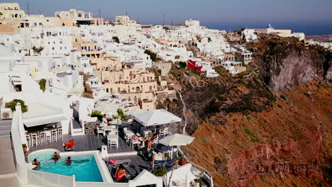 Multi-colored-houses-line-the-hillsides-of-the-Greek-Island-of-Santorini-with-a-Greek-flag-in-the-distance-3