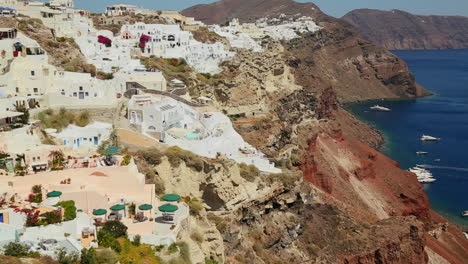 Slow-pan-of-white-houses-lining-the-hillsides-of-the-Greek-Island-of-Santorini-with-a-Greek-flag-in-the-distance-1