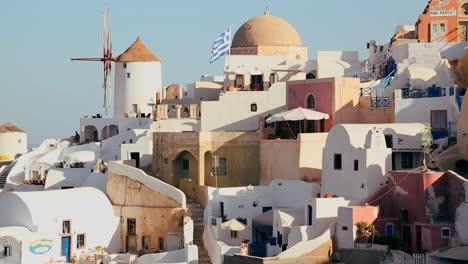 Los-Edificios-Blancos-Y-Los-Molinos-De-Viento-Se-Alinean-En-Las-Laderas-De-La-Isla-Griega-De-Santorini-Con-Una-Bandera-Griega-En-La-Distancia-1