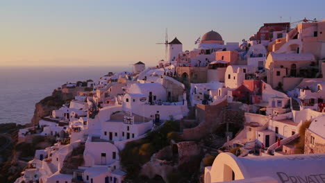 White-buildings-and-windmills-line-the-hillsides-of-the-Greek-Island-of-Santorini-at-dusk