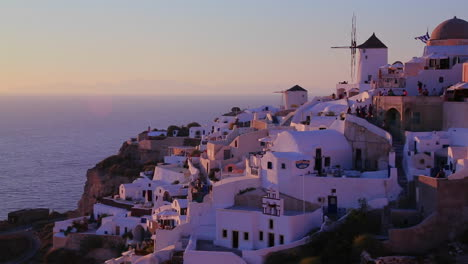 White-buildings-and-windmills-line-the-hillsides-of-the-Greek-Island-of-Santorini-at-dusk-2