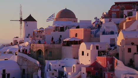 White-buildings-and-windmills-line-the-hillsides-of-the-Greek-Island-of-Santorini-at-dusk-3