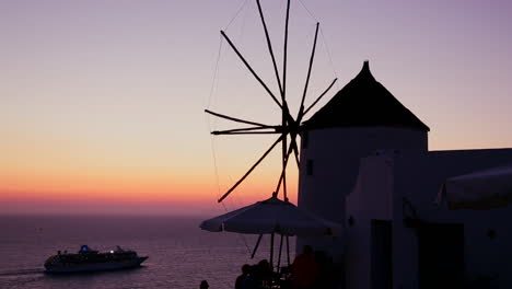 A-cruise-ship-passes-windmills-at-dusk-or-sunset-on-the-romantic-Greek-Island-of-Santorini-at-dusk-1