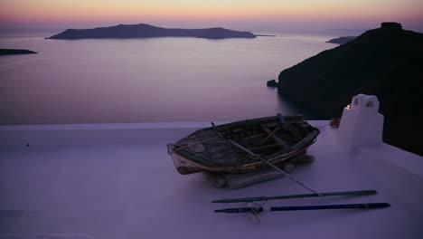 Un-Bote-De-Remos-Se-Asienta-Sobre-Un-Techo-Frente-A-Una-Hermosa-Atardecer-Detrás-De-Las-Islas-En-Las-Islas-Griegas