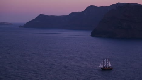 A-beautiful-sailing-ship-sails-near-some-islands-at-night