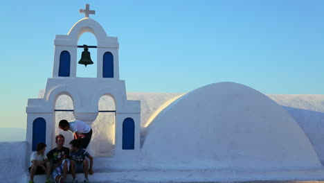 Kids-sit-on-the-white-roof-of-a-Greek-Orthodox-Church