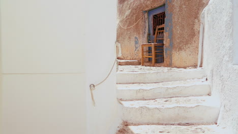 Chairs-sit-in-a-white-alley-on-the-island-of-Santorini-in-Greece