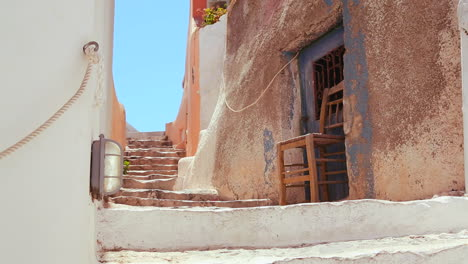 Chairs-sit-in-a-white-and-brown-alley-on-the-island-of-Santorini-in-Greece