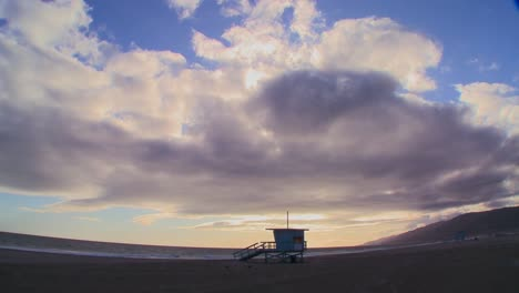 Time-lapse-of-a-cloud-formations-moving-behind-a-lifeguard-station-on-a-Los-Angeles-beach