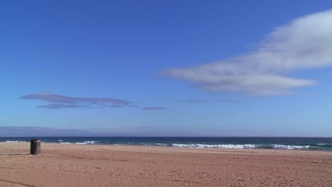 An-empty-beach-with-a-lone-garbage-can-and-blue-sky