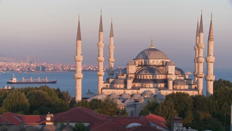 The-Blue-Mosque-in-Istanbul-Turkey-at-dusk-with-cargo-ship-background