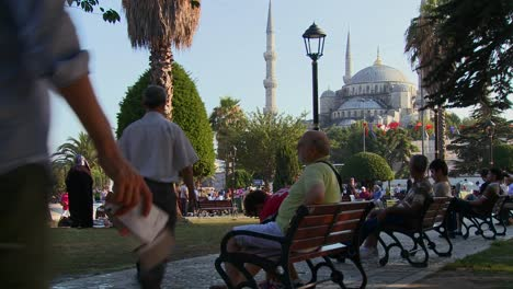 Pedestrians-walk-and-sit-on-benches-near-the-Blue-Mosque-in-istanbul-Turkey