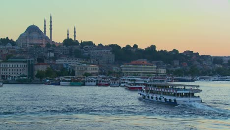 Boats-pass-in-the-harbor-in-front-of-the-mosques-of-Istanbul-Turkey-at-dusk