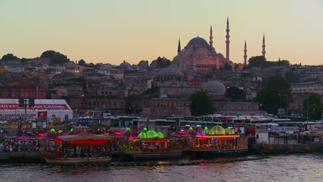 Colorful-boats-bob-in-the-water-at-dusk-in-front-of-a-mosque-in-Istanbul-Turkey