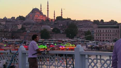 Pescador-Y-Coloridos-Barcos-Al-Atardecer-En-Frente-De-Una-Mezquita-En-Estambul-Turquía
