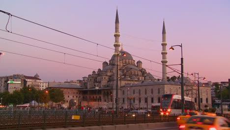 Tranvías-De-Tránsito-Rápido-Y-El-Tráfico-Al-Anochecer-En-Frente-De-Una-Mezquita-En-Estambul-Turquía