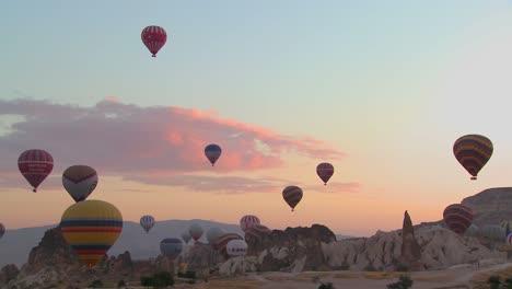 Hot-air-ballons-rise-from-the-desert-floor-against-a-beautiful-sky-in-Cappadocia-Turkey