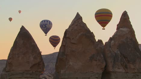 Three-hot-air-balloons-are-beautifully-silhouetted-against-a-mountain-peak-in-Cappadocia-Turkey-1