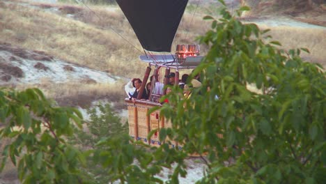 Passengers-ride-in-a-hot-air-balloon-that-is-almost-skimming-the-ground