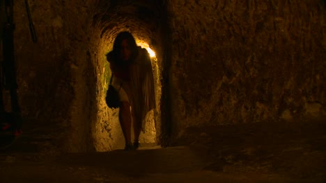 A-woman-walks-in-a-tunnel-or-cave-in-an-underground-city-near-Cappadocia-Turkey