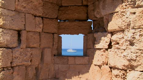 A-sailboat-is-perfectly-framed-through-a-castle-wall-in-Rhodes-Greece