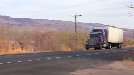 A-long-distance-truck-drives-on-a-road-through-the-desert