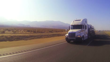 A-car-carrier-truck-moves-across-the-desert-in-this-POV-shot