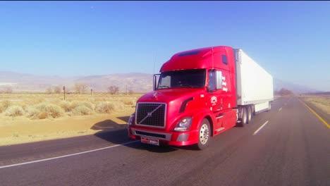 A-red-18-wheeler-truck-moves-across-the-desert-in-this-POV-shot