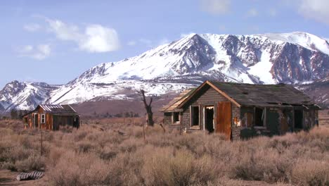 Time-lapse-of-the-snowcapped-Sierra-Nevada-mountains-with-abandoned-ghost-town-cabins-in-the-Eastern-part-of-California