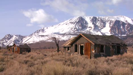 Abandoned-settler-cabins-with-the-snowcapped-Sierra-Nevada-mountains-with-the-sun-shining-through-clouds