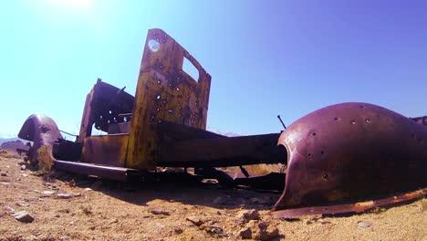 Dolly-shot-beside-an-abandoned-pickup-truck-in-the-desert-sun