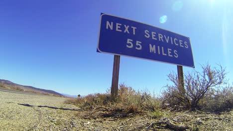 Ein-Schild-An-Einer-Einsamen-Wüstenstraße-Warnt-Dass-Die-Nächsten-Dienste-55-Meilen-Entfernt-Sind-1