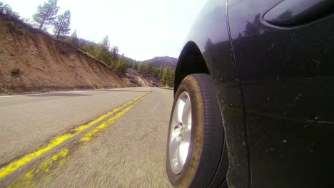 POV-shot-driving-along-a-highway-with-side-of-car-and-wheel-visible