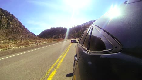 POV-shot-driving-fast-along-a-mountain-road-with-the-car-visible