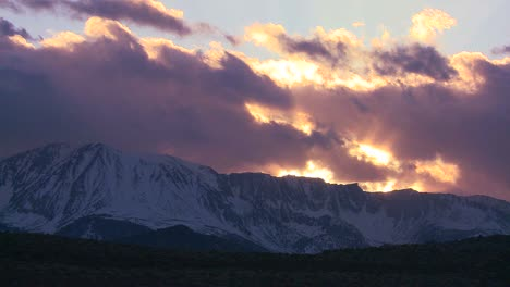 Time-lapse-of-the-snowcapped-Sierra-Nevada-mountains-with-the-sun-shining-through-clouds