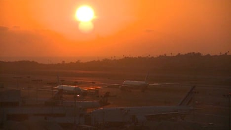 Planes-taxi-at-sunset-or-sunrise-at-a-major-metropolitan-airport