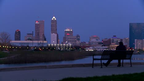 A-man-sits-on-a-park-bench-overlooking-the-city-of-Indianapolis-at-dusk