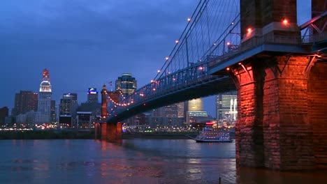 A-riverboat-travels-at-night-with-the-Cincinnati-Ohio-skyline-background