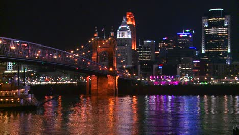 Luz-reflects-off-the-Ohio-Río-with-the-city-of-Cincinnati-Ohio-background-as-a-riverboat-passes-underneath