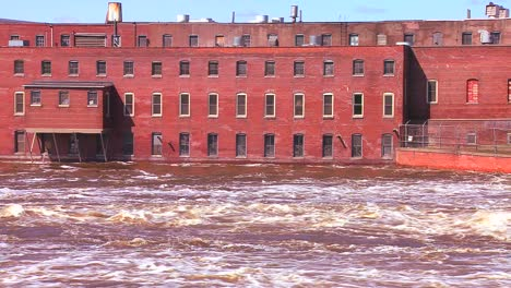A-flooding-river-flows-past-an-old-factory