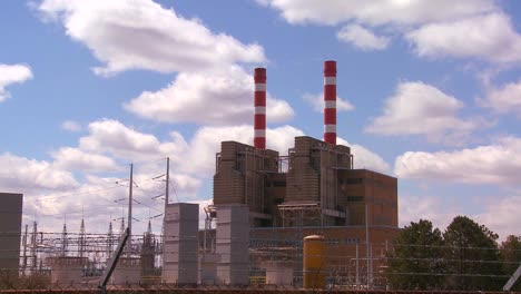 A-power-plant-with-striped-towers-with-clouds-moving-behind