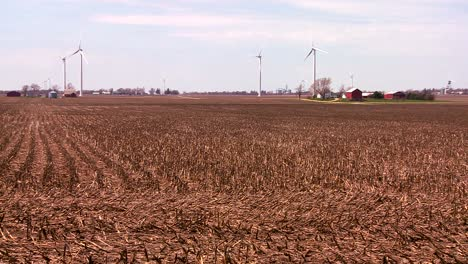 Giant-windmills-in-the-distance-generate-power-behind-farms-in-the-American-midwest