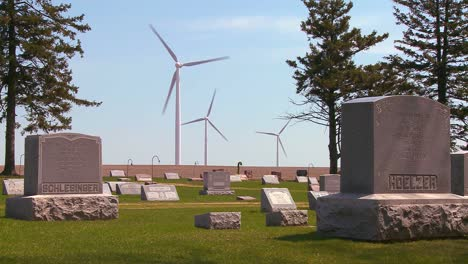 Giant-windmills-in-the-distance-generate-power-behind-farms-in-the-American-midwest-Graveyard-or-cemetery-foreground